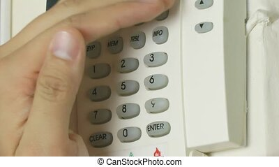 Turning on alarm system with hands covering the pin code