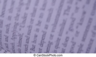 Turning pages of an open book close up. English tex is blurry. Slow motion