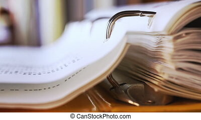 Turning pages of a yellow ring binder, underline a page with a pink pencil ,in the foreground steel ring binder in focus , in the background out of focus books and folders