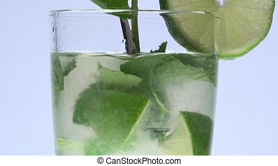 Turning stirrer stick in a mojito - closeup with white...