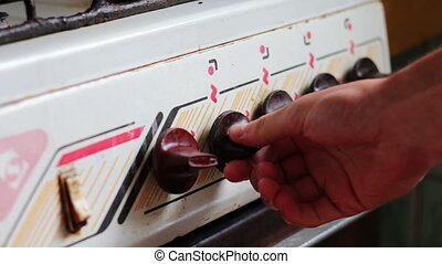 Turning the knob on the gas stove.