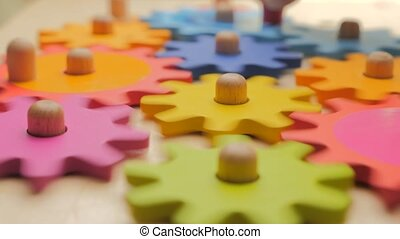 Turning toy wooden gears. Gears and cogs macro in colorful ...