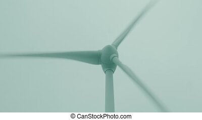 Turning wind turbine rotor, low angle close-up shot -...