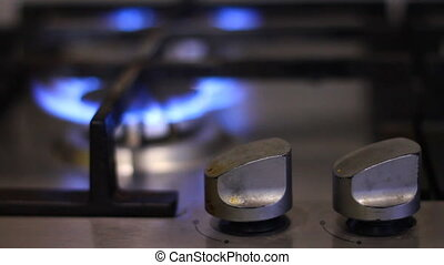 Turns on gas stove with burning flame