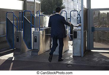 turnstile in the underground - The man passes through a...