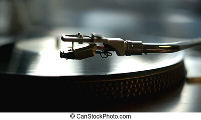 Turntable with spinning vinyl records. Turntable stylus going down.