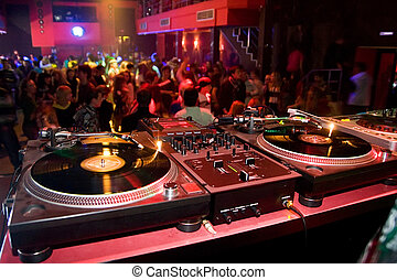 Djs table with audio equipment in the crowded club