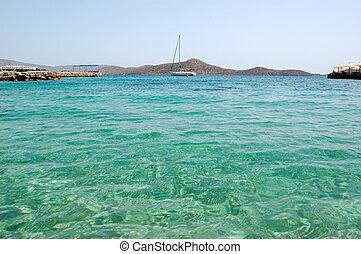 Turquoise Aegean Sea near beach of luxury hotel with yacht view, Crete, Greece