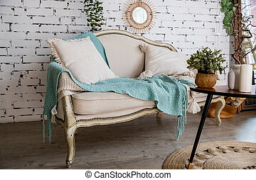 Turquoise blanket and pillows standing on beige soga in stylish apartment interior with brick wall background.bright room interior with wooden table with plant.