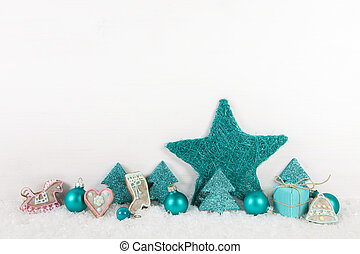Turquoise christmas decoration on wooden background with snow.