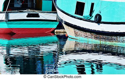 Close up of turquoise Fischer boats reflecting in the water