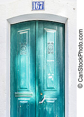 Turquoise door illuminated by sun reflection in Lisbon,...