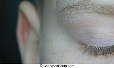 Turquoise eyes of blond boy teenager with red freckles on...