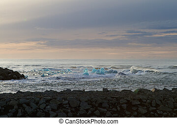 Turquoise ice in the water, by the black beach at Jokulsarlonm Iceland