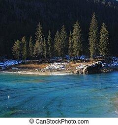 Turquoise ice on lake Cauma and fir trees