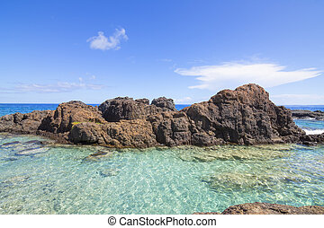 Turquoise pool on rocky tropical sea shore