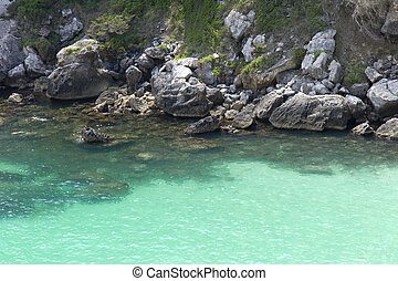 Turquoise sea, transparent on the coast of Menorca at the foot of a cliff.