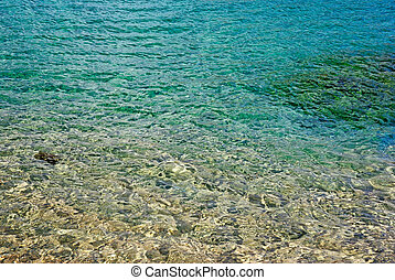 Turquoise shiny sea water on a sunny day near the shore.