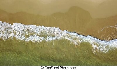 Turquoise surf of the sea waves on yellow sand. Aerial survey