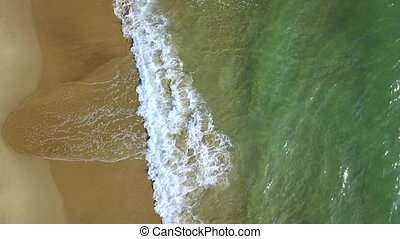 Turquoise waves on a shore turn into of foaming. Aerial...