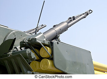 Turret with two large caliber machine guns aimed at blue sky. Close-up.