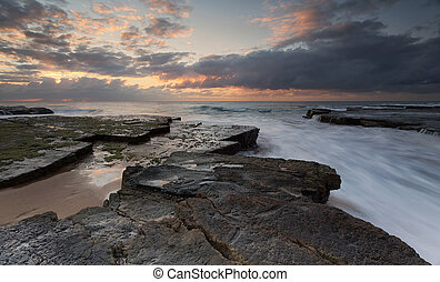Fast moving ocean rock flows just after sunrise at the southern end of Turrimetta rockshelf on Sydney's northern beaches.