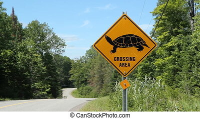 Turtle crossing. - Yellow, diamond shaped sign warns of...