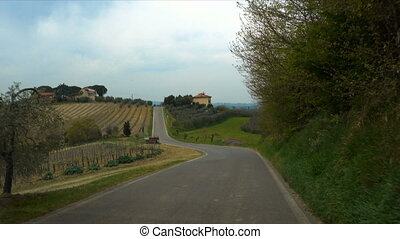 tuscanian hills through the windscreen of car on a road