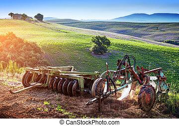 Tuscany landscape at sunrise. Retro agriculture machines. Italy