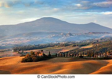 Tuscany landscape at sunrise. Tuscan farm house, cypress trees, hills.