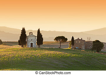 Tuscany landscape at sunrise with a little chapel of Madonna di Vitaleta, Italy.