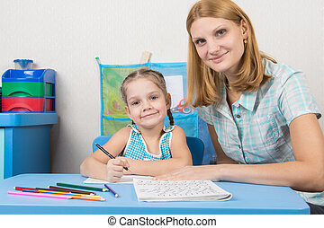 Tutor and five year old girl engaged in spelling