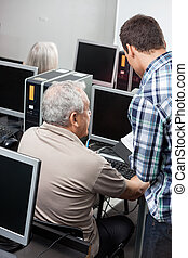 Tutor Assisting Senior Man In Using Computer At Classroom