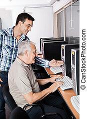 Tutor Assisting Senior Man In Using Computer