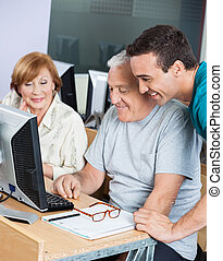 Tutor Assisting Senior Students In Using Computer At Classroom