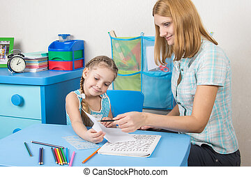 Tutor checks the job done on a piece of a five-year girl