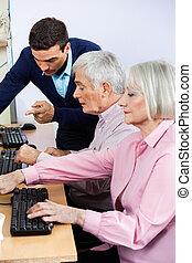 Tutor Explaining Senior Students Using Computers In Classroom