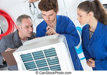 tutor instructing trainee electricians