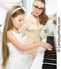 Tutor teaches little pianist to play piano