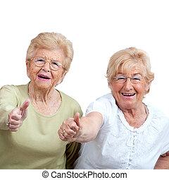 två, äldre kvinna, visande, tummar, uppe.