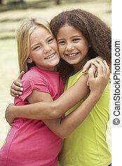 två flickor, i park, ge sig, varandra, kram