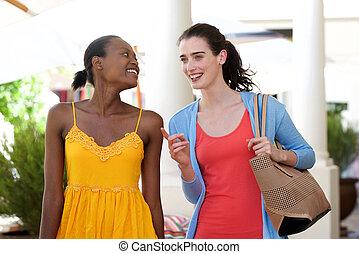 två kvinnor, gående och prata, utanför