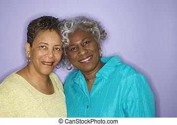 två kvinnor, le.