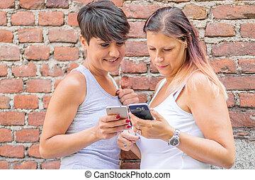 två, le, hålla ögonen på, smartphone, kvinna, videos