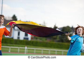 två pojkar, spring, på, fotboll gärde, med, tyska flagga