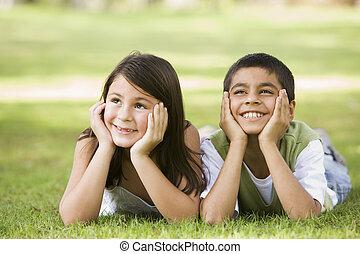 två, unga barn, utomhus, lögnaktig, i park, le, (selective,...