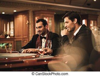 två, unga herrar i kostymer, bak, hasardspel, bord, in, a,...