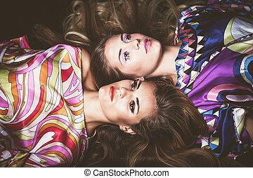två, unga kvinnor, med, länge, blont hår, skönhet, mode, stående, lägga sig ner