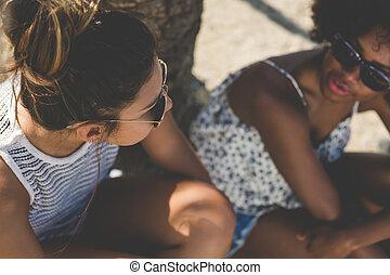 två, unga kvinnor, sittande, och, talande, utanför