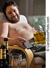 TV addicted man sitting in chair with a beer glass and remote control